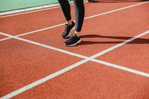 Female runner legs at stadium