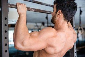 Man tightening on horizontal bar at gym