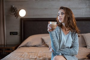Woman sitting on the bed and drinking coffee
