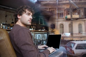 Pensive handsome man using laptop with blank screen