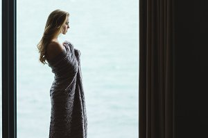 Beautiful thoughtful female with long hair standing in knitted coverlet