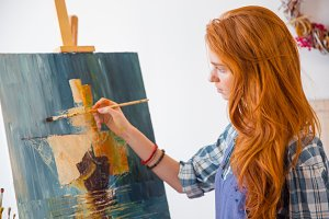 Beautiful serene young female painter painting picture in art workshop