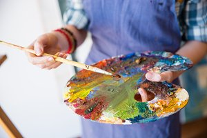Palette with mixed paints holded by hands of woman artist