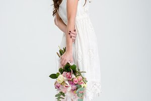 Beautiful woman in white dress and roses wreath standing barefoot