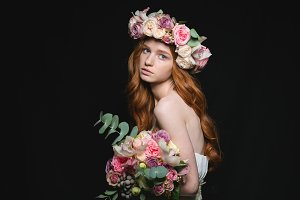 Attrative redhead woman posing with flowers