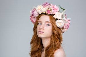 Closeup of attractive young redhead female in beautiful rose wreath