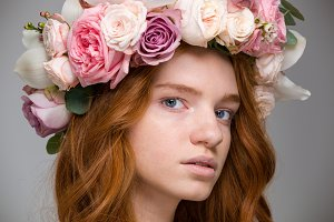 Gentle beautiful girl with red hair in wreath of roses