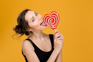 Lovely playful woman licking sweet heart shaped lollipop