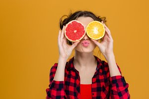 Funny playful woman holding halves of citrus fruits against eyes