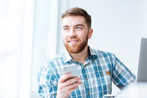Happy man using smartphone and looking away