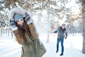 Beautiful happy couple throwing snowballs and having fun