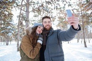 Couple making selfie photo in winter park