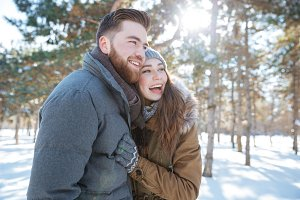Cheerful couple standing in winter park