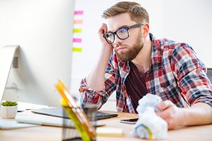 Bored exhausted man sitting on workplace and looking at monitor