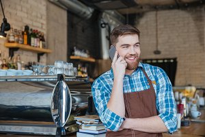 Cheerful waiter with beard talking on mobile phone in cafeteria