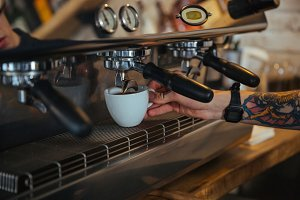 Coffee machine making coffee in cup holded by barista hand