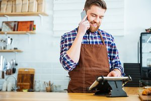 Barista taking order on cellphone and using tablet in cafeteria