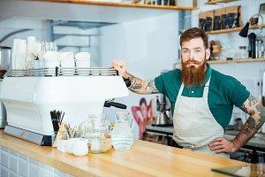 Portrait of barista standing near coffe machine in coffee shop