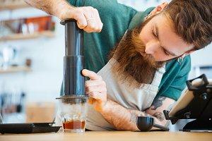 Barista preparing coffee with press