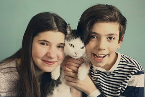 teen siblings boy and girl cuddle with cat