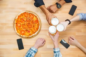 Multiethnic group of young people drinking beer and eating pizza