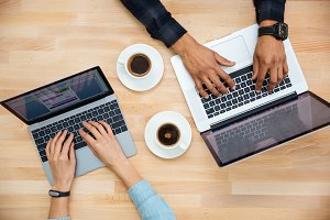Hands of african man and caucasian woman typing on laptops