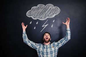 Angry man standing and shouting over blackboard with drawn raincloud