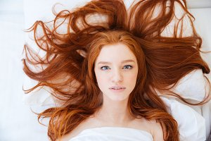 Woman with beautiful long red hair lying in bed