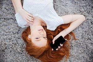 Redhead woman listening music on smartphone