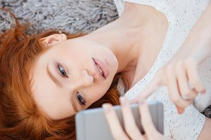Woman lying on the carpet with smartphone