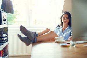 Cute young woman with feet on table