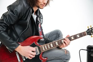Closeup of concentrated young man playing electric guitar