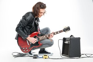 Focused handsome young guitarist playing electric guitar with amplifier