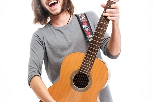 Excited handsome young man with long hair playing acoustic guitar