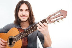 Attractive happy young man smiling and holding acoustic guitar