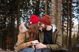 Young happy loving couple sitting over forest and hugging