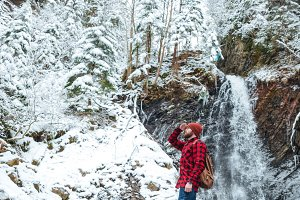 Attractive bearded young man walking near mountain waterfall in winter