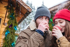 Man and woman drinking hot coffee on christmas market