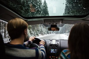 Beautiful couple driving in car through winter forest