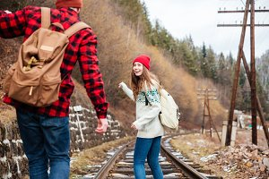 Couple talking and walking on railroad together