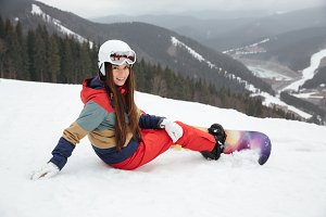 Pretty lady snowboarder lies on the slopes frosty winter day.