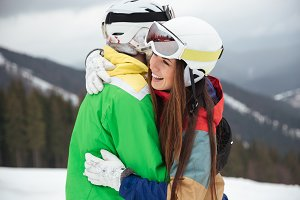 Loving couple snowboarders on the slopes hugging