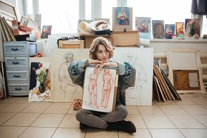 Woman artist sitting in art studio and showing her drawings