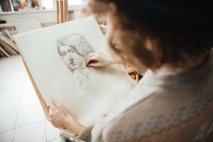Woman artist drawing man portrait using black crayon in workshop