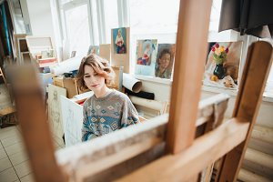Thoughtful woman painter painting using wooden easel in workshop