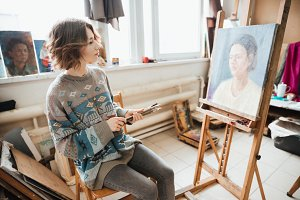 Attractive pensive woman painter painting picture in art studio
