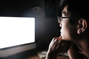 Concentrated man in glasses looking at blank screen of computer