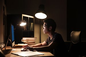 Serious man using computer and typing in dark room