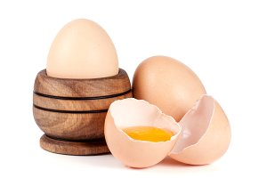 two whole eggs and broken egg in a wooden bowl isolated on white background