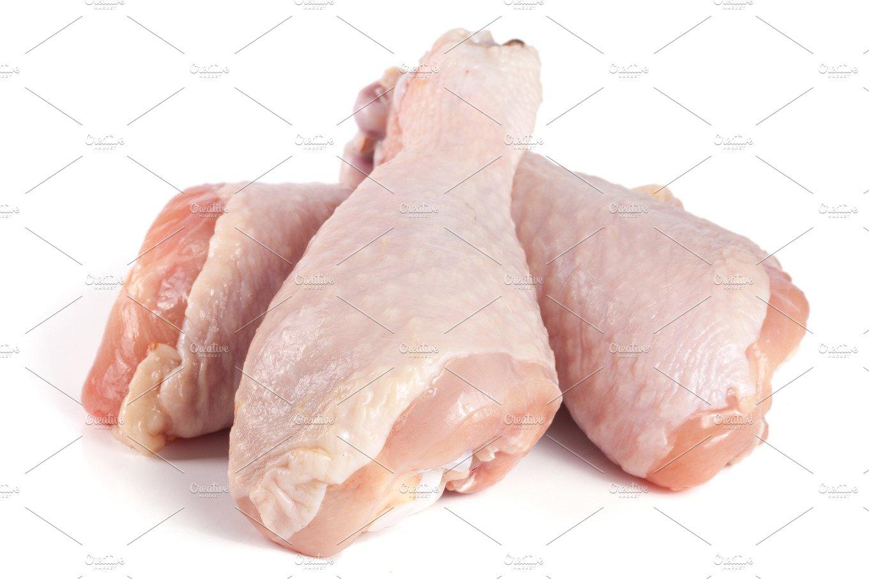 Three raw chicken drumsticks isolated on white background ...